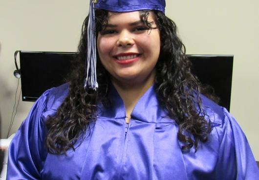 HOPE student smiles for the camera after trying on her cap and gown