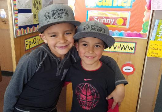 Elementary students pose for the camera in their new HOPE hats