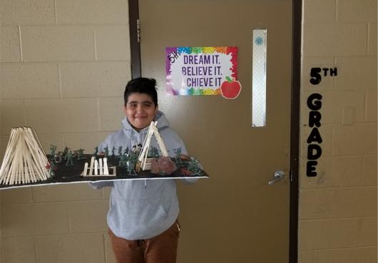 Student displays classroom project he created.